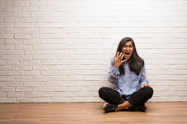 Young indian woman sit against a brick wall very scared and afraid, desperate for somethin