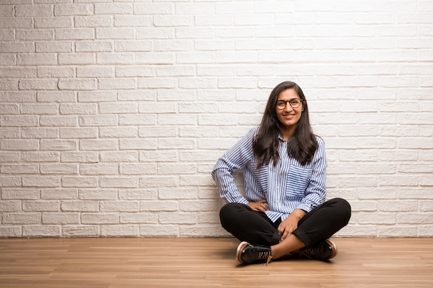 Young indian woman sit against a brick wall with hands on hips, standing, relaxed and smiling
