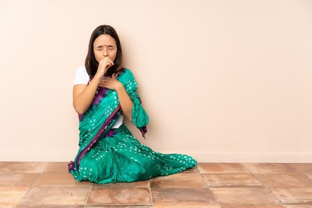 Молодая индийская женщина сидит на полу и много кашляет