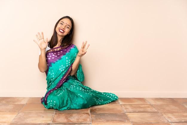指で8を数える床に座っている若いインド人女性