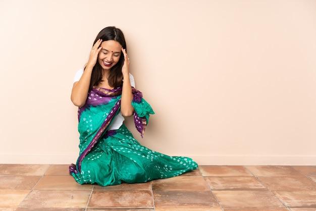 笑って床に座っている若いインド人女性