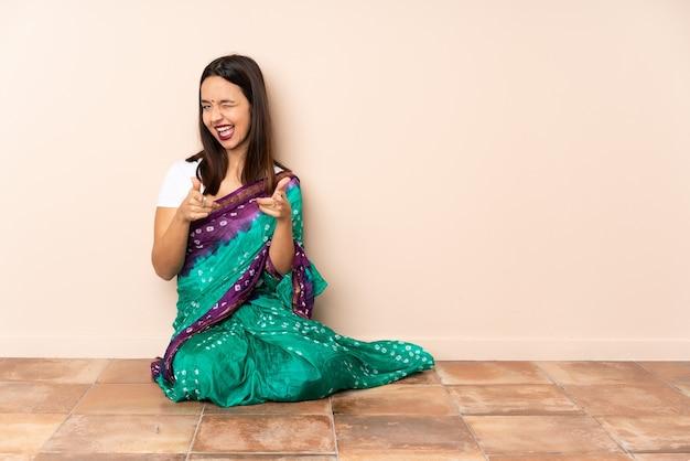正面を向いて笑顔で床に座っている若いインド人女性