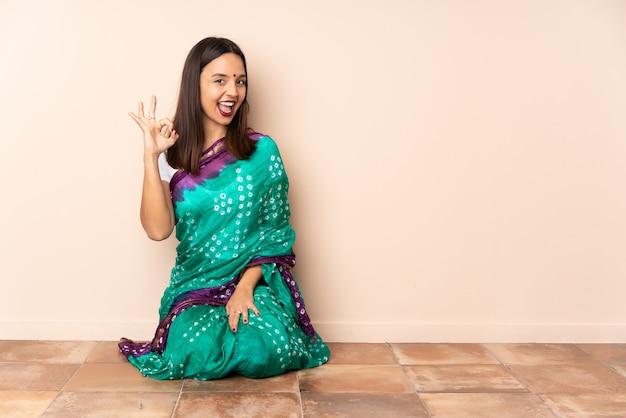 指でokの標識を示す床に座っている若いインド人女性