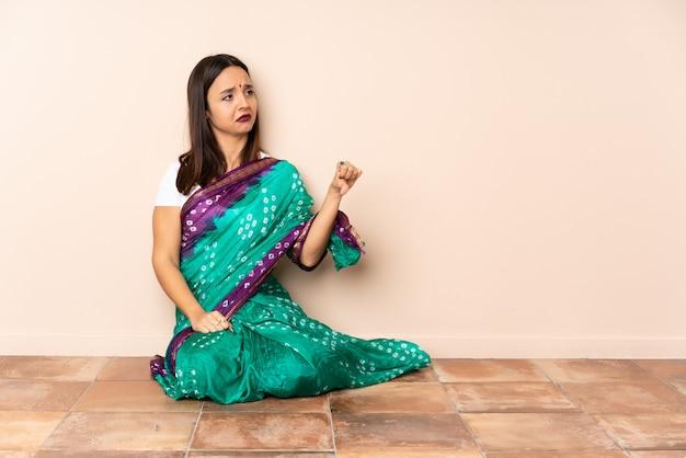 Молодая индийская женщина, сидя на полу, показывая большой палец вниз с негативным выражением