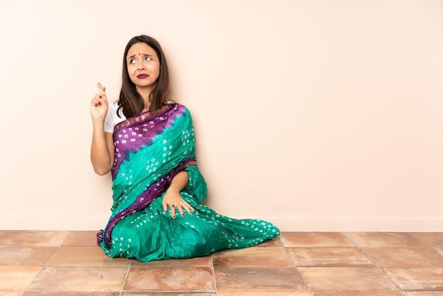 指を交差させて床に座って、最高を願って若いインドの女性