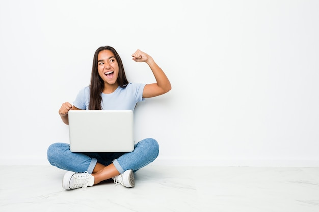 Young indian woman sitting working on laptop raising fist after a victory
