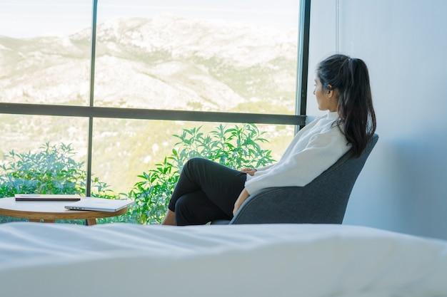 Молодая индийская женщина думает на стуле рядом с ее кроватью