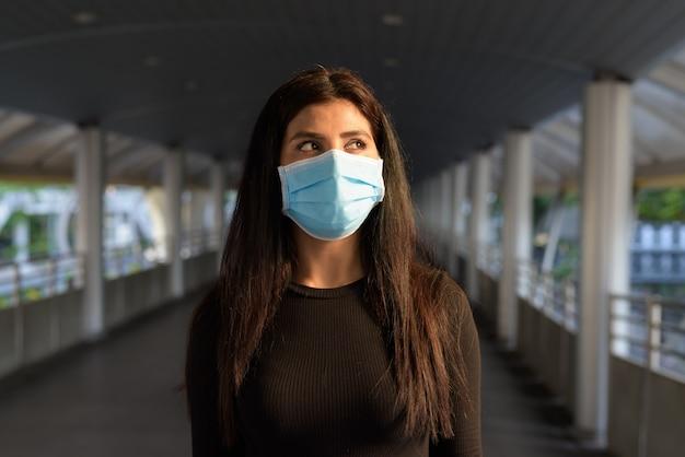 인도교에서 코로나 바이러스 발생으로부터 보호하기 위해 마스크로 생각하는 젊은 인도 여성