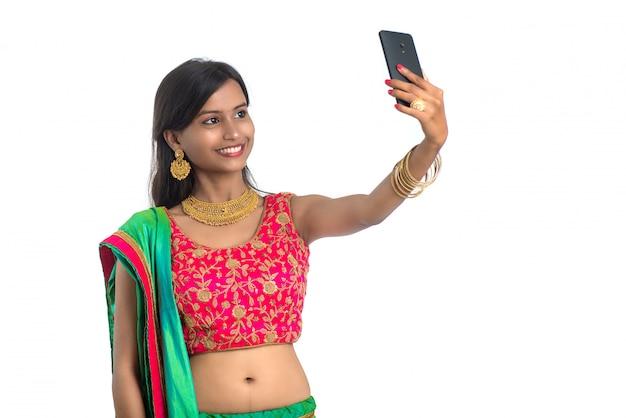 Молодая индийская женщина с помощью планшета, мобильного телефона или смартфона, изолированные на белом