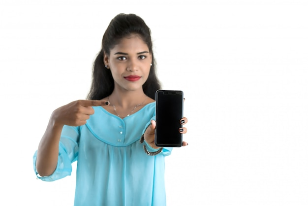 Young indian woman using a mobile phone or smartphone isolated on a white wall