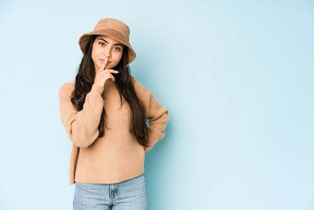 青い背景に分離された帽子をかぶった若いインド人女性は、考え、見上げ、反射し、熟考し、ファンタジーを持っています。