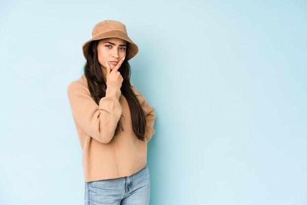 Молодая индийская женщина в шляпе, изолированной на синей стене, размышляя, планируя стратегию, думая о способе ведения бизнеса.