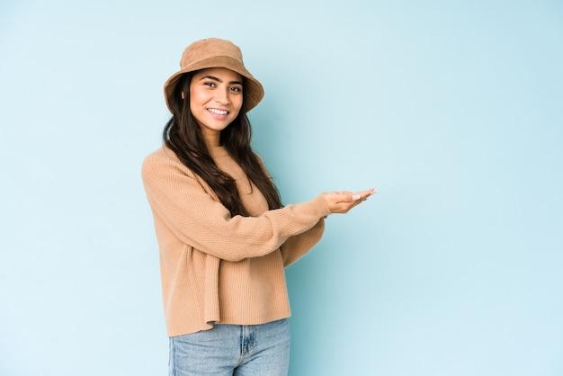 Молодая индийская женщина в шляпе, изолированной на синей стене, держащей копию пространства на ладони.