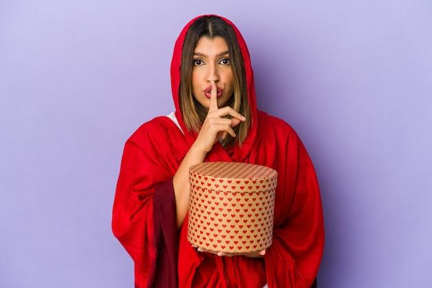 秘密を守るか、沈黙を求めて孤立したバレンタインデーの贈り物を保持しているヒジャーブを身に着けている若いインドの女性。