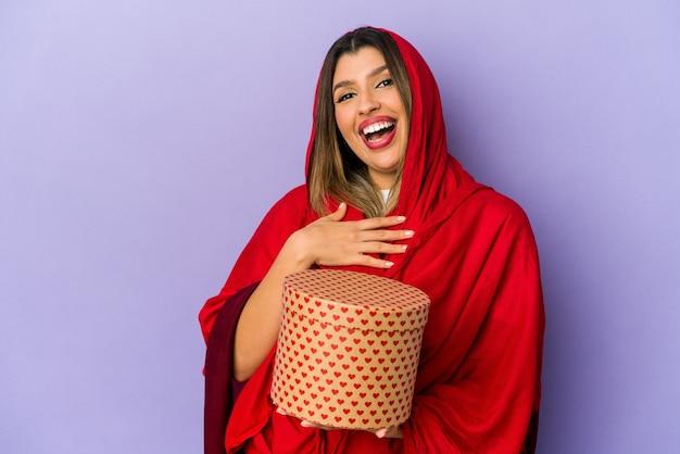 Молодая индийская женщина в хиджабе, держащая изолированный подарок на день святого валентина, громко смеется, держа руку на груди.
