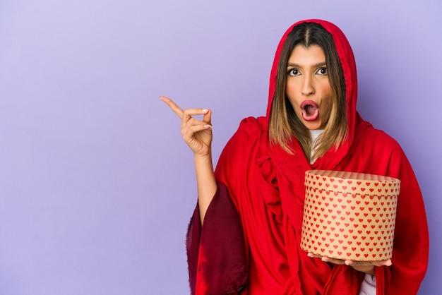 Молодая индийская женщина в хиджабе с подарком на день святого валентина изолирована, указывая в сторону
