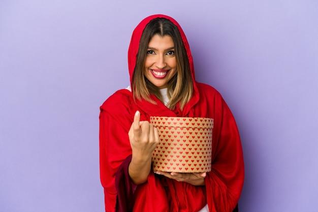Молодая индийская женщина в хиджабе, держащая подарок на день святого валентина, изолировала, указывая пальцем на вас, как будто приглашая подойти ближе.