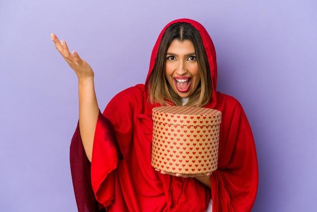Молодая индийская женщина в хиджабе, держащая подарок на день святого валентина, изолировала получая приятный сюрприз, взволновала и подняла руки.