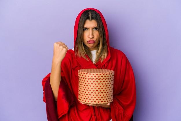 카메라, 공격적인 표정에 주먹을 보여주는 절연 발렌타인 데이 선물을 들고 hijab를 입고 젊은 인도 여자.