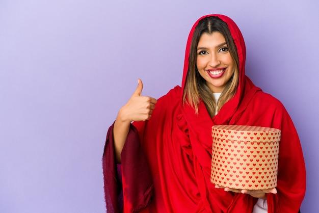 Молодая индийская женщина в хиджабе с подарком на день святого валентина изолирована, улыбаясь и поднимая палец вверх