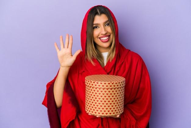 Молодая индийская женщина в хиджабе, держащая подарок на день святого валентина, изолировала, улыбаясь, веселый показ номер пять с пальцами.