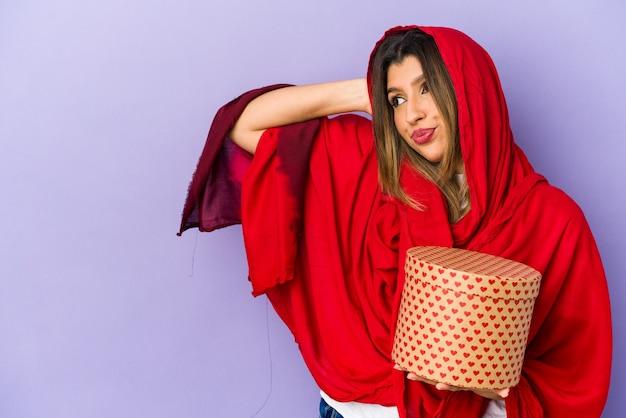 Молодая индийская женщина в хиджабе, держащая подарок на день святого валентина, изолировала прикосновение к затылку, думая и делая выбор.