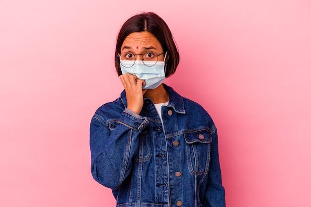 Молодая индийская женщина в антивирусной маске, изолированной на розовом фоне, кусает ногти, нервничает и очень тревожится.