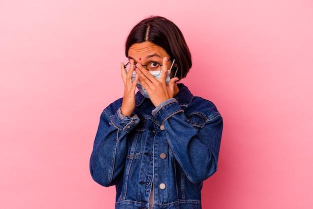Молодая индийская женщина в антивирусной маске, изолированной на розовом фоне, моргает сквозь пальцы, испугавшись и нервнича.