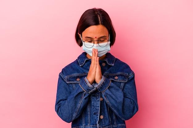 입 근처기도에 손을 잡고 분홍색 배경에 고립 된 마스크 바이러스 백신을 입고 젊은 인도 여자는 자신감을 느낀다.