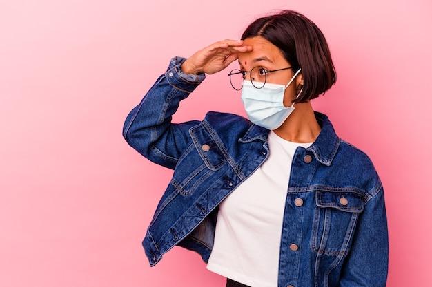 Молодая индийская женщина, носящая антивирусную маску, изолированную на розовом фоне, смотрит далеко, держа руку на лбу.