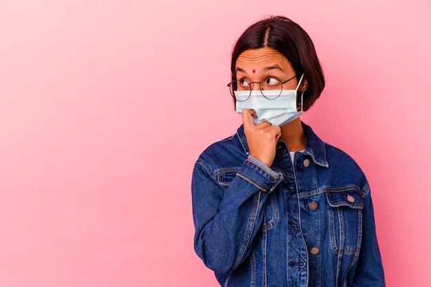 분홍색 배경에 고립 된 마스크 바이러스 백신을 입고 젊은 인도 여자 복사본 공간을보고 뭔가에 대해 편안 하 게 생각.