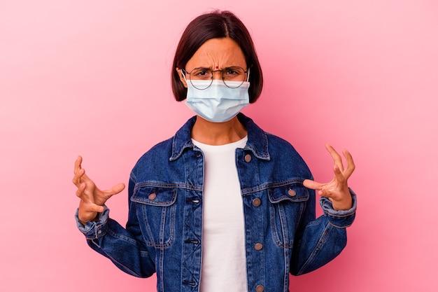 Молодая индийская женщина в антивирусной маске, изолированной на розовом, кричит от ярости.
