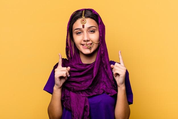 노란색 배경에 고립 된 전통적인 사리 옷을 입고 젊은 인도 여자는 빈 공간을 보여주는 두 앞 손가락으로 나타냅니다.