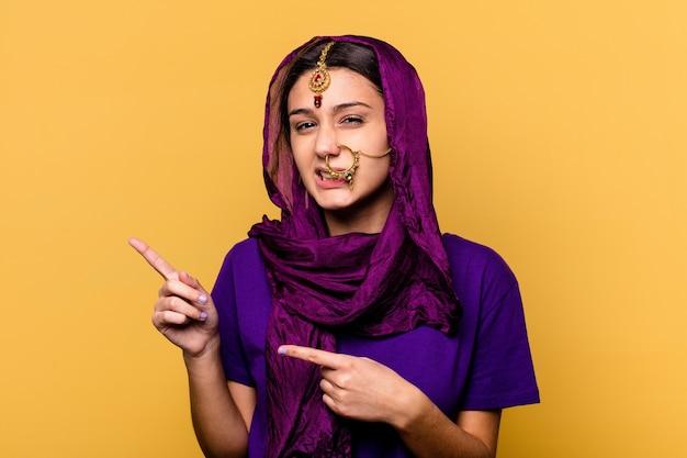 Молодая индийская женщина в традиционной одежде сари, изолированной на желтом, потрясена, указывая указательными пальцами на место для копирования.