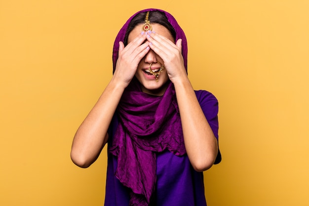 노란색 벽에 고립 된 전통적인 사리 옷을 입고 젊은 인도 여자는 손으로 눈을 덮고, 미소는 놀라움을 광범위하게 기다리고 있습니다.
