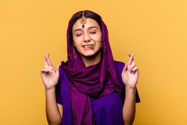 행운을 갖는 노란색 벽 횡단 손가락에 고립 된 전통적인 사리 옷을 입고 젊은 인도 여자