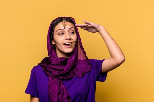 멀리 이마에 손을 유지 찾고 노란색 벽에 고립 된 전통적인 사리 옷을 입고 젊은 인도 여자.