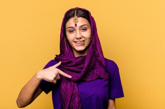Молодая индийская женщина в традиционной одежде сари изолирована на желтой стене человека, указывая рукой на место для копирования рубашки, гордая и уверенная в себе