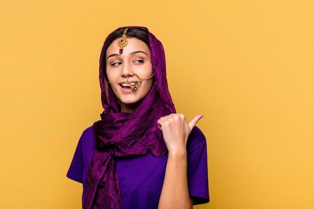 親指の指を離れて黄色の壁のポイントに分離された伝統的なサリーの服を着て、笑ってのんきなインドの若い女性