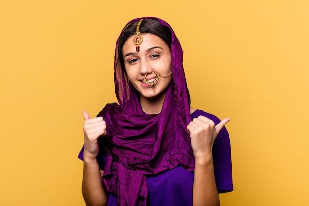노란색 벽에 고립 된 전통적인 사리 옷을 입고 젊은 인도 여성, 두 엄지 손가락을 높이고 웃고 자신감