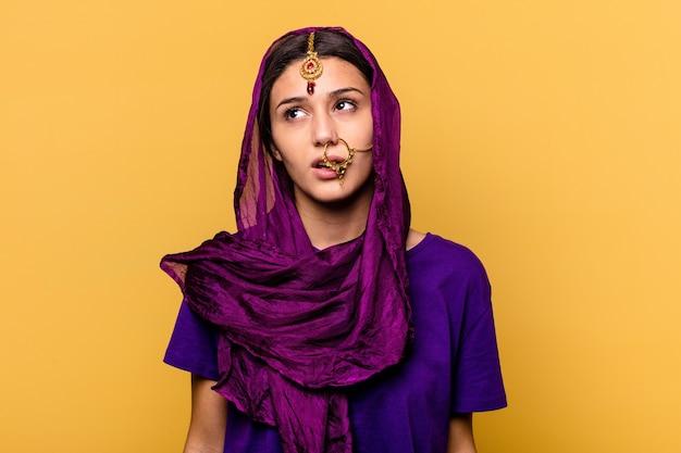 繰り返しの作業にうんざりしている黄色の壁に隔離された伝統的なサリーの服を着ている若いインドの女性