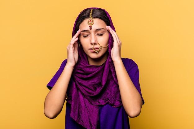 寺院に触れて頭痛を持っている黄色の壁に隔離された伝統的なサリーの服を着ている若いインドの女性。