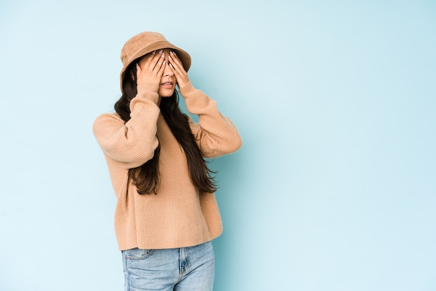 Young indian woman wearing a hat afraid covering eyes with hands.