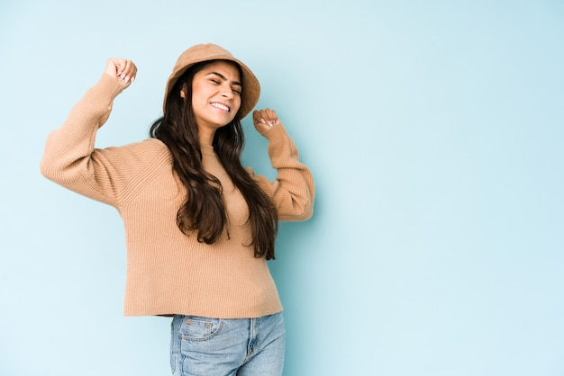 Young indian woman wearing a hat on blue wall raising fist after a victory