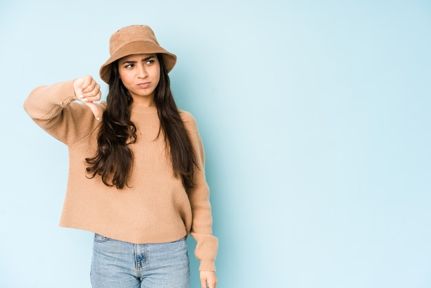 Young indian woman wearing a hat showing thumb down and expressing dislike.