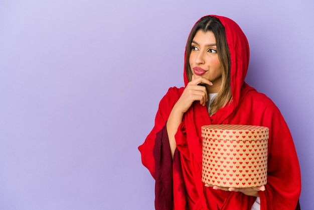 Young indian woman wearing a hijab holding a valentines day gift isolated looking sideways with doubtful and skeptical expression.
