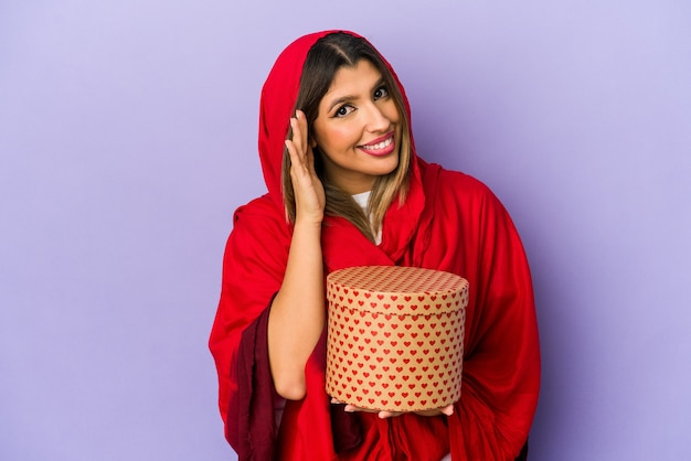 Young indian woman wearing a hijab holding a valentines day gift isolated trying to listening a gossip.