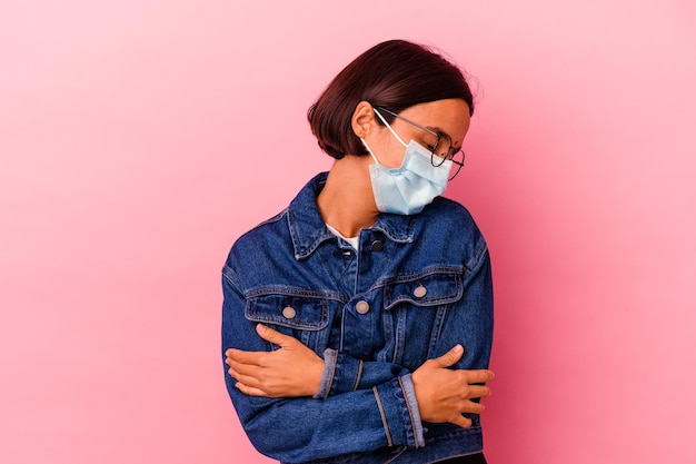 Young indian woman wearing a mask antivirus isolated on pink hugs, smiling carefree and happy. Premium Photo