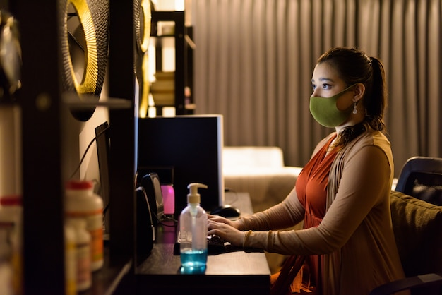 Young indian woman wearing mask while working from home late at night