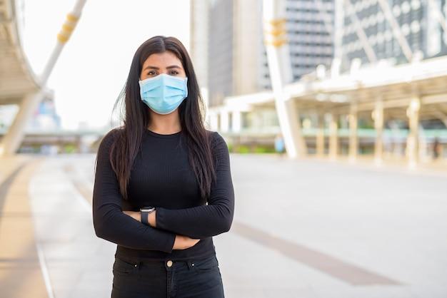팔으로 마스크를 쓰고 젊은 인도 여자는 skywalk 다리에서 넘어